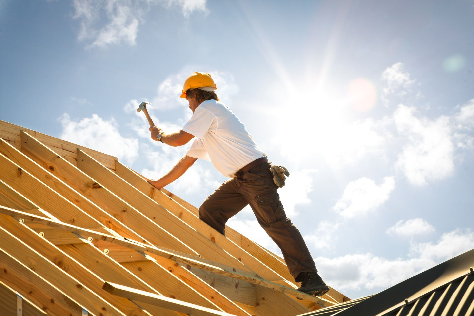 A man working on a roof following all health and safety guidelines possible.
